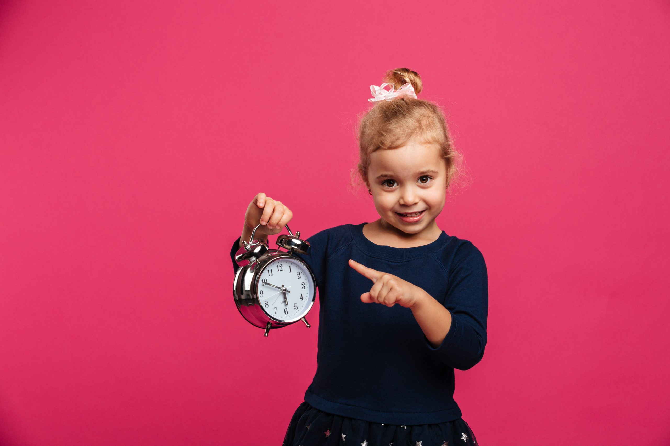 Happy young girl holding alarm clock and pointing on it